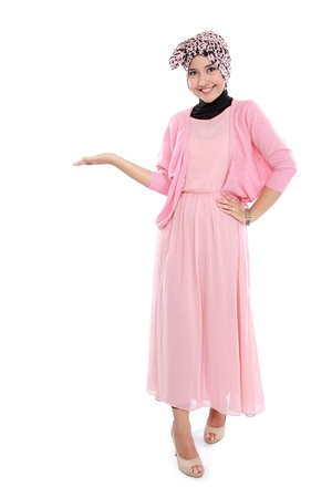 Portrait of standing young muslim woman showing blank area for sign or copyspace photo