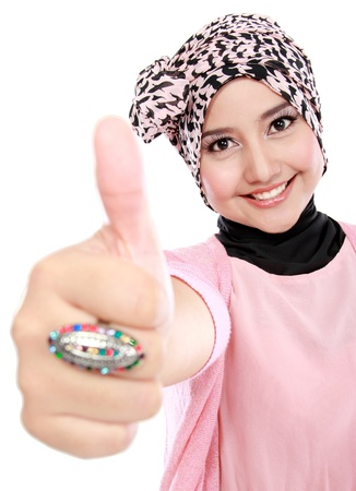 Beautiful young muslim woman giving thumbs up isolated over white background photo