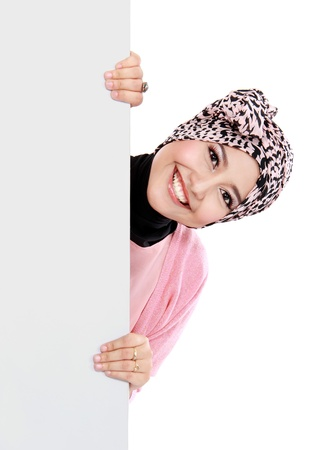 'muslim: Portrait of happy attractive muslim woman holding a blank white board isolated over white background