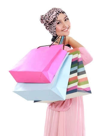 Happy of attractive young muslim woman with shopping bag isolated over white background photo