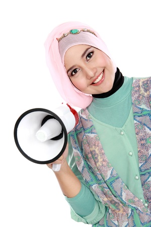 Young attractive muslim woman holding megaphone over white background photo