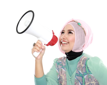 Young attractive muslim woman shouting using megaphone isolated over white background photo