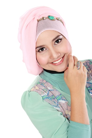 Portrait of a happy young asian muslim woman in action and looking at camera