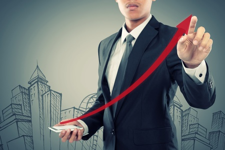 Businessman drag a rising arrow at smartphone, representing business growth, on virtual background. photo