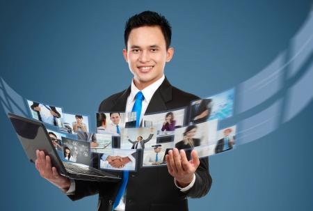 réseautage: Portrait de jeune homme d'affaires partage ses fichiers photo et vidéo utilisant un ordinateur portable