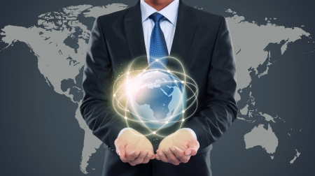Business man holding the small world in his hands against world map background photo