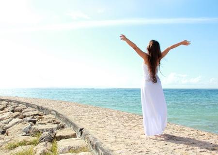 Femme de détente à la plage avec les bras ouverts appréciant sa liberté porter longue robe blanche