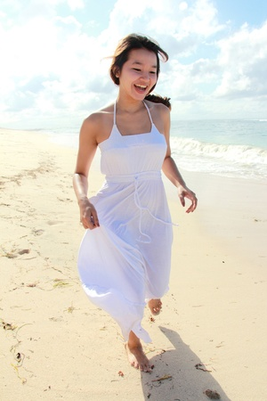 Young happy woman with white long dress running on the beach Stock Photo - 22008329