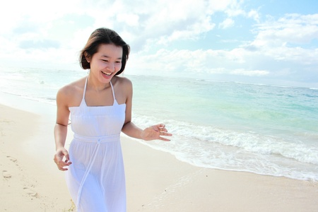 Young happy woman with white long dress running on the beach Stock Photo - 22008333