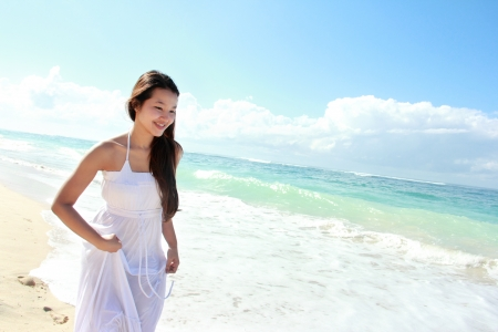 Young happy woman with white long dress running on the beach Stock Photo - 22008340
