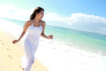 Young happy woman with white long dress running on the beach Stock Photo - 22008342