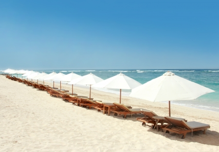 lounge chairs and umbrellas at the beautiful beach photo