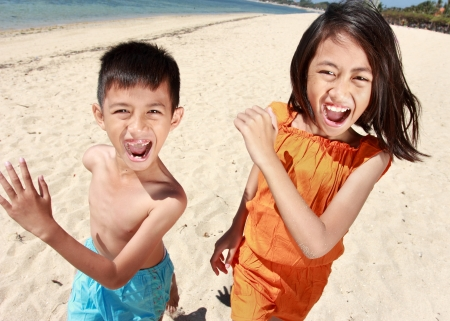 Portrait of happy little boy and girl running in the beach together Stock Photo