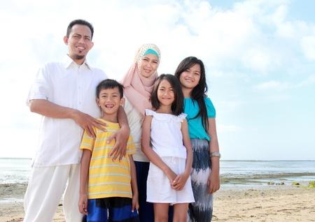 petite fille musulmane: Sourire famille asiatique heureux à la plage ensemble et en regardant la caméra