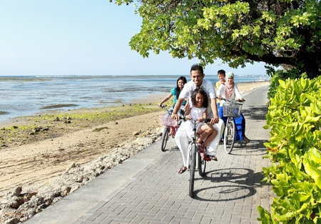 moslem: Happy asian family riding bikes in the beautiful morning at the beach. Outdoor portrait Stock Photo