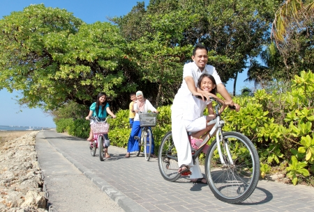 familia abrazo: Familia asi�tica feliz andar en bicicleta en la hermosa ma�ana en la playa. Retrato al aire libre Foto de archivo