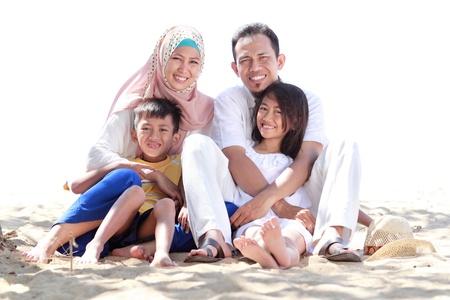 해변에서 행복 무슬림 가족의 초상화와 카메라를 찾고