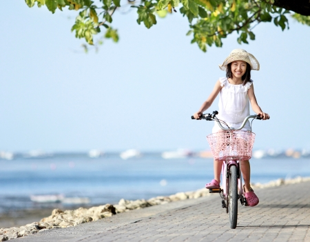 bicycle girl: Portrait of happy attractive litte girl wearing a hat riding bicycle outdoor