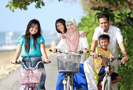 moslem: Portrait of happy muslim family with kids enjoy riding bicycle outdoor in the beach