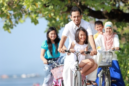 Portrait of happy muslim family with kids enjoy riding bicycle outdoor in the beach