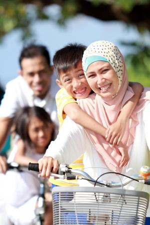 아름 다운 화창한 날에 함께 자전거를 타고 행복 무슬림 가족의 초상화 스톡 콘텐츠