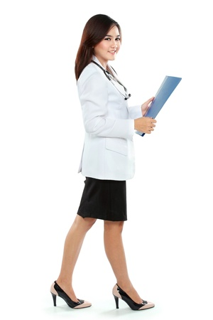 Young woman doctor in lab coat holding clipboard isolated over white background photo