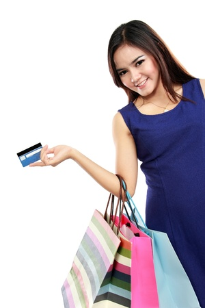 Beautiful woman holding shopping bags and credit card isolated on white background photo