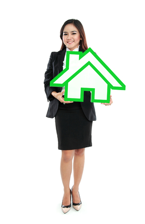 Smiling businesswoman holding house sign  photo