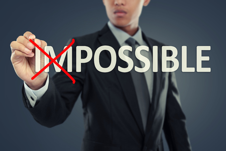 Businessman changing word impossible into possible on virtual background photo