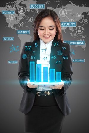 Image of businesswoman in black suit showing graph over world background photo
