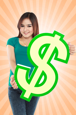 Portrait of beautiful young woman holding dollar sign photo