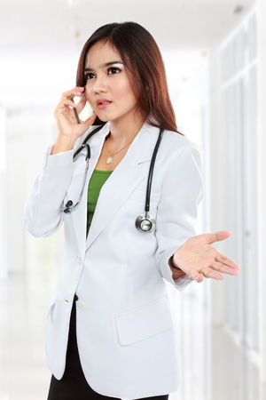 Attractive female doctor in lab coat with stethoscope talking by cellphone in hospital photo