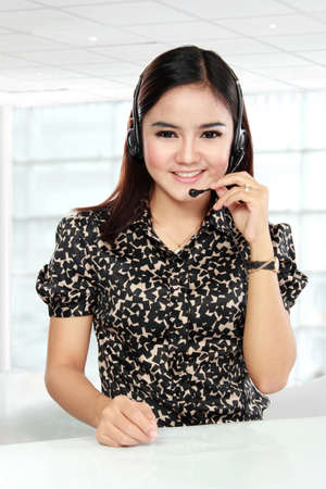 Busy businesswoman in office place communicate by wireless headset over white table. Stock Photo - 22535646