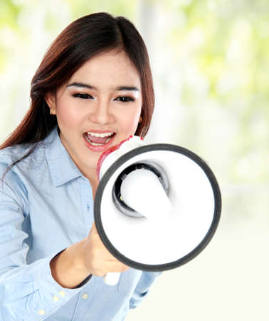Portrait of young attractive asian woman shouting with a megaphone photo