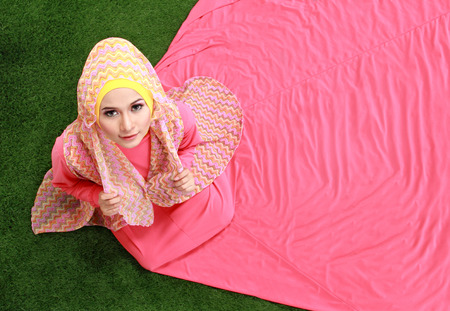 Young muslim girl wearing hijab sitting on grass