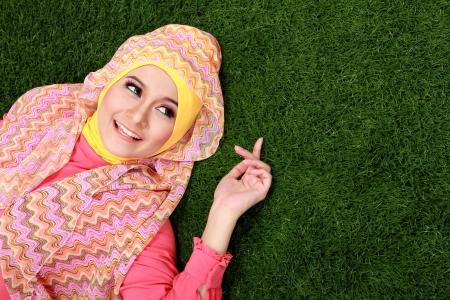 dívka: Mladá muslimská dívka, která nosí hidžáb ležící na trávě