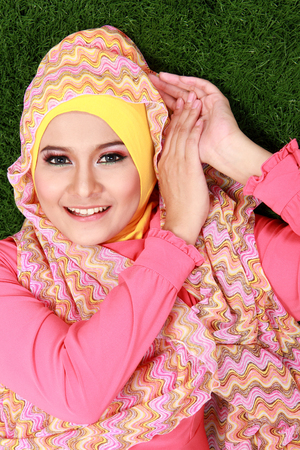 pretty Young muslim woman wearing hijab lying on grass photo