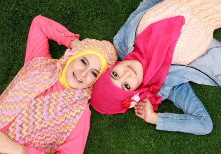two beautiful happy muslim woman smiling lying on grass photo