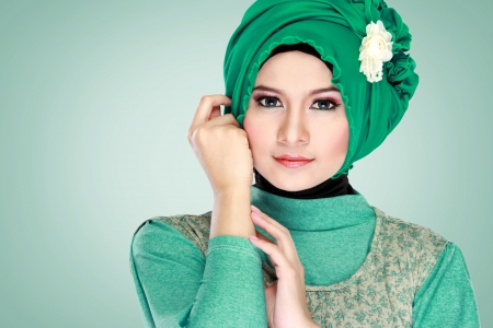 muslimah: Fashion portrait of young beautiful muslim woman with green costume wearing hijab