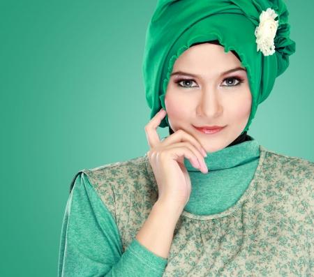 hijab: Fashion portrait of young beautiful muslim woman with green costume wearing hijab