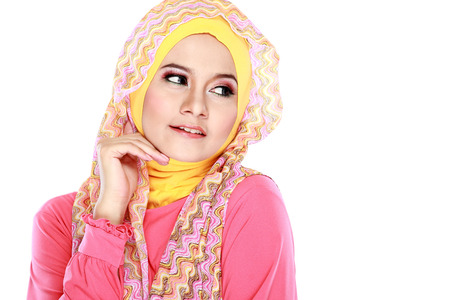 Fashion portrait of young beautiful muslim woman with pink costume wearing hijab