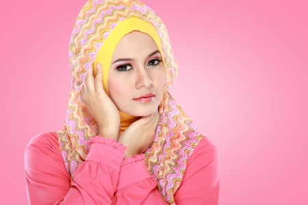 Fashion portrait of young beautiful muslim woman wearing pink photo