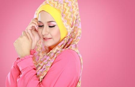 ヒジャーブを身に着けているピンクの衣装で若い美しいイスラム教徒の女性のファッションの肖像画