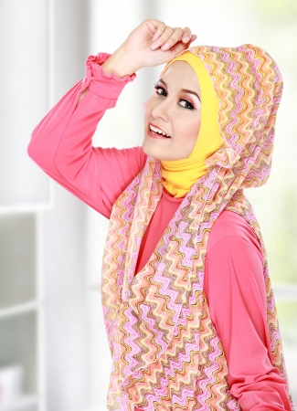 portrait of beautiful happy muslim woman smiling in her room photo