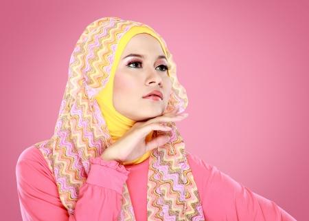 Fashion portrait of young beautiful muslim woman with pink costume wearing hijab photo