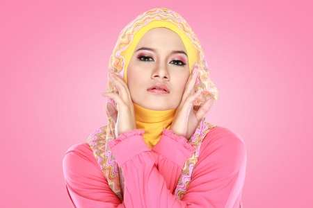 ヒジャーブを着ているピンクのコスチュームの若い美しいアジア ムスリム女性のファッションの肖像画
