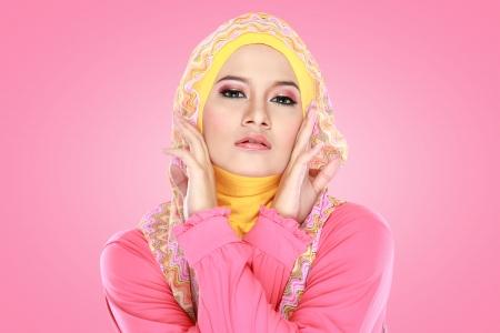 hijab 착용 핑크 의상과 함께 아름다운 아시아 이슬람 여자의 패션 초상화 스톡 콘텐츠