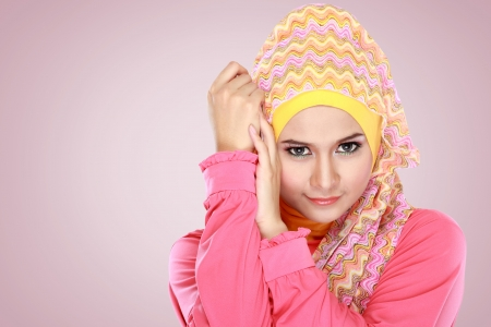 Fashion portrait of young beautiful muslim woman with pink costume wearing hijab photo