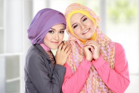 Portrait of two beautiful muslim woman having fun at home photo