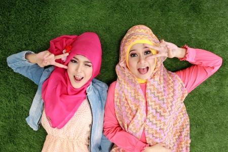 두 아름 다운 행복 한 이슬람 여자는 잔디에 누워 미소